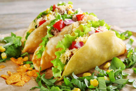 background food: Tasty taco with greens on paper close up