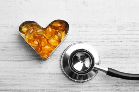 cod oil: Heart of cod liver oil and stethoscope, on wooden background