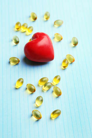 cod oil: Red heart and cod liver oil, on blue background