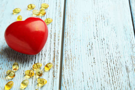cod oil: Red heart and cod liver oil on blue wooden background