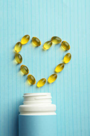 cod oil: Heart of cod liver oil and jar with capsules on blue background Stock Photo