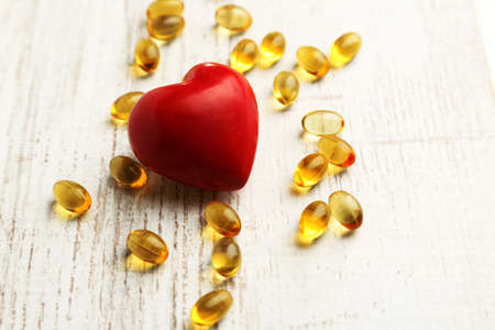 cod oil: Red heart and cod liver oil, on wooden background Stock Photo