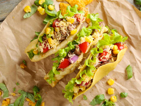food ingredient: Tasty taco with greens on paper close up