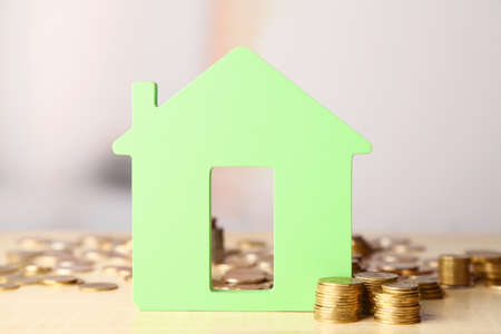 money stack: Model of house with coins on bright background