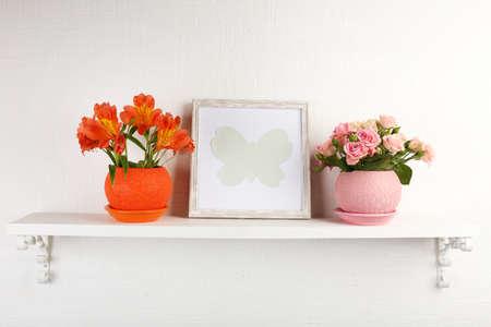 decorative wall: Beautiful flowers in pots on shelf on wall background