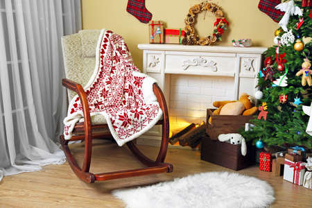 hearthside: Living room with Christmas tree, fireplace and rocking chair Stock Photo
