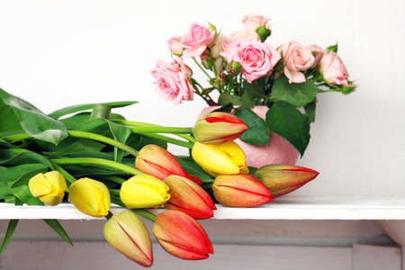 shelf: Beautiful flowers on shelf on wall background Stock Photo