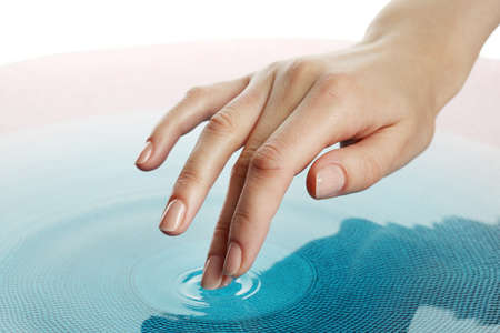 dedo: Dedo toca de cerca al agua hasta Foto de archivo