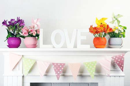 mantelpiece: Beautiful flowers in ornamental flowerpot on mantelpiece