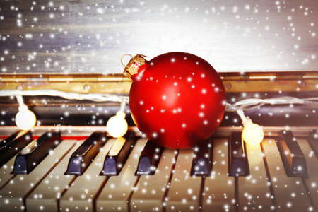 Piano keys decorated with decoration lights and red ball, close up Фото со стока