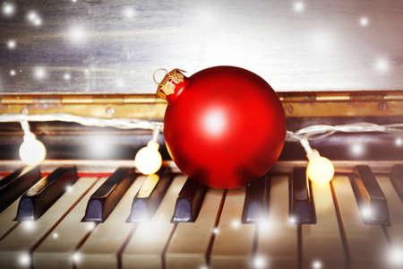 Piano keys decorated with decoration lights and red ball, close up Stock Photo