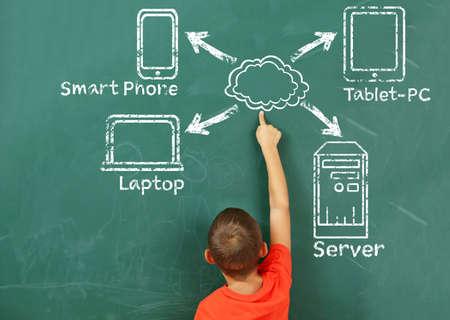 Little boy drawing cloud network on the chalkboard Stock Photo