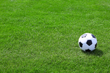 outfield: Soccer ball on green field Stock Photo