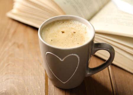 Stillleben mit einer Tasse Kaffee und Buch, auf Holztisch
