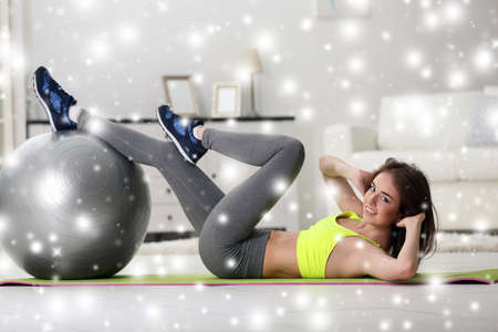 fit ball: Beautiful young girl doing exercises with fit ball at home over snow effect