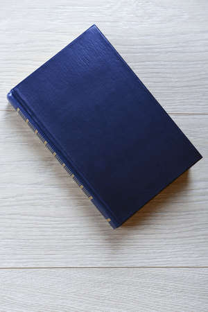 single story: Old book on wooden background