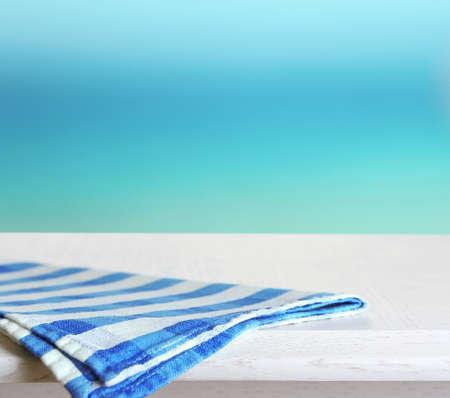 white napkin: White wooden table with napkin on blue background