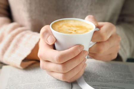 holding close: Woman holding cup of coffee and read the book, close up