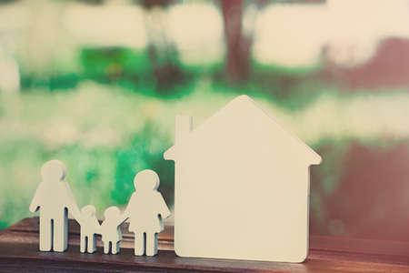 Pequeño modelo de la casa y de la familia en el fondo borroso