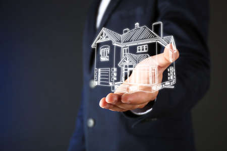 artificial model: Real estate offer. Businessman holds an artificial model of the house