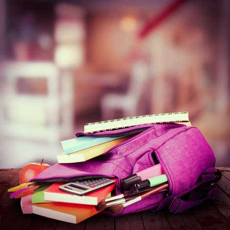 school desk: School backpack on wooden desk, on abstract background