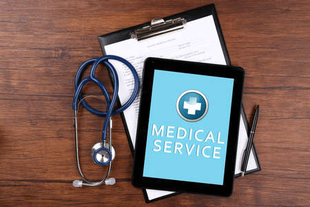 online service: Tablet-pc on doctor table, concept of medical service