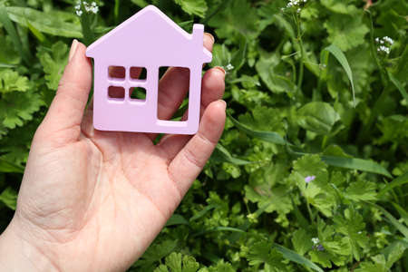 toy house: Female hand holding toy house outdoors Stock Photo