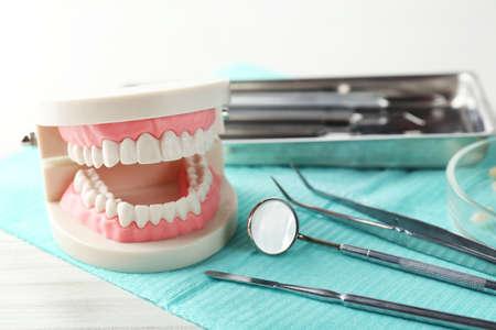 Weiße Zähne und zahnärztliche Instrumente auf dem Tisch Hintergrund Standard-Bild