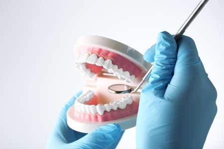 odontologa: dientes falsos blancas en la mano del dentista, aislados en blanco