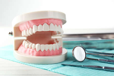 medical practice: White teeth and dental instruments on table background