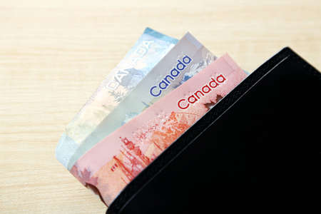 fondos violeta: Male wallet with Canadian dollars on wooden table Foto de archivo
