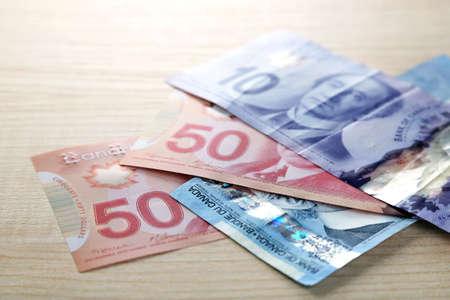 fondos violeta: d�lares canadienses en mesa de madera