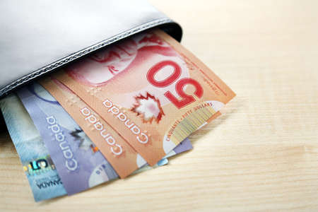 50 dollar bill: Male wallet with Canadian dollars on wooden table Stock Photo