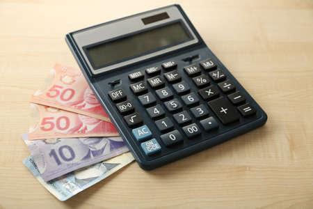 fondos violeta: Calculadora y d�lares canadienses, en mesa de madera