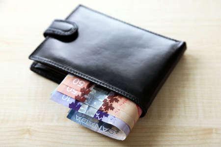 fondos violeta: billetera masculina con los d�lares canadienses en mesa de madera Foto de archivo