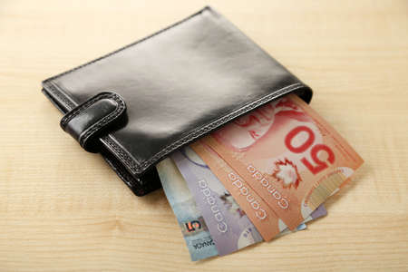 Male wallet with Canadian dollars on wooden table Stock Photo