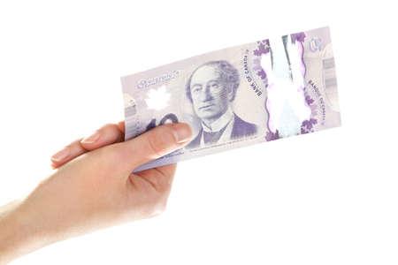 fondos violeta: Mano femenina con 10 Dólar canadiense, aislado en blanco