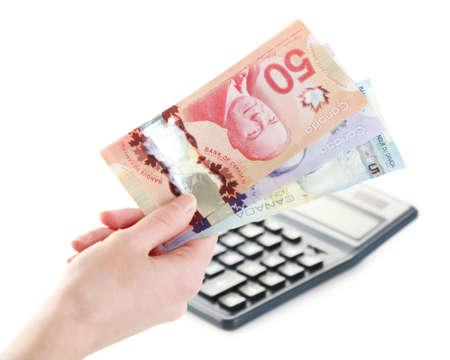 main Femme avec des dollars canadiens et calculatrice, isolé sur blanc
