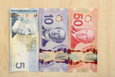 fondos violeta: Canadian dollars on wooden table