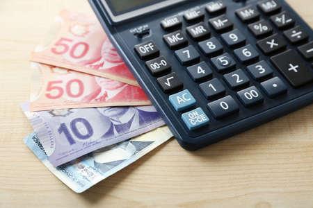 fondos violeta: Calculadora y dólares canadienses, en mesa de madera