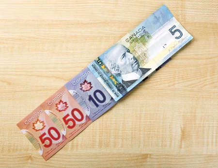 fondos violeta: dólares canadienses en mesa de madera