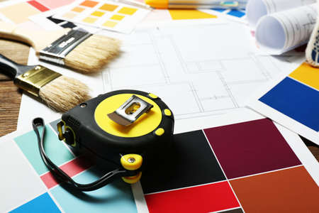 painter and decorator: Construction instruments, plan and brushes on wooden table background