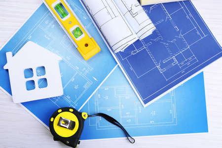 architectural plan: Construction instruments, plan and brushes over house plan on wooden table background Stock Photo