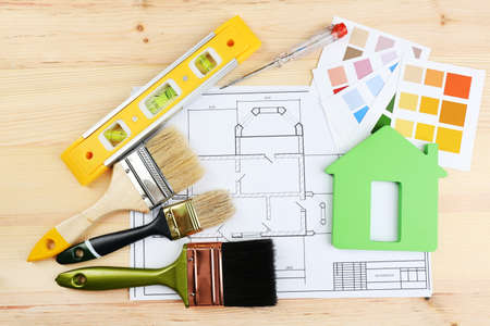 construction material: Construction instruments, plan, color samples and brushes on wooden table background