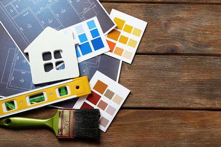 Farbmuster, dekorative Haus, Handschuhe und Pinsel auf Holztisch Hintergrund