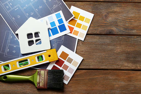Color samples, decorative house, gloves and paintbrushes on wooden table background Archivio Fotografico