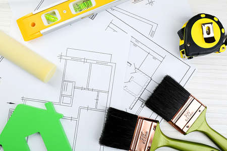 plans: Construction instruments, plan and brushes on wooden table background