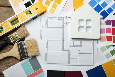 home plans: Construction instruments, plan and brushes on wooden table background