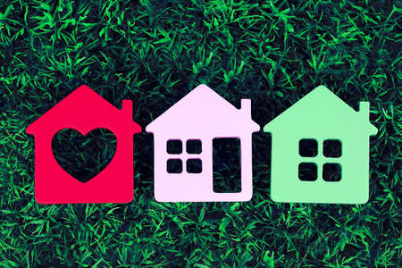 Toy houses on grass background, close-up