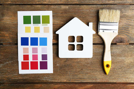 paint samples: Colorful paint samples, decorative house  and paintbrushes on wooden table background